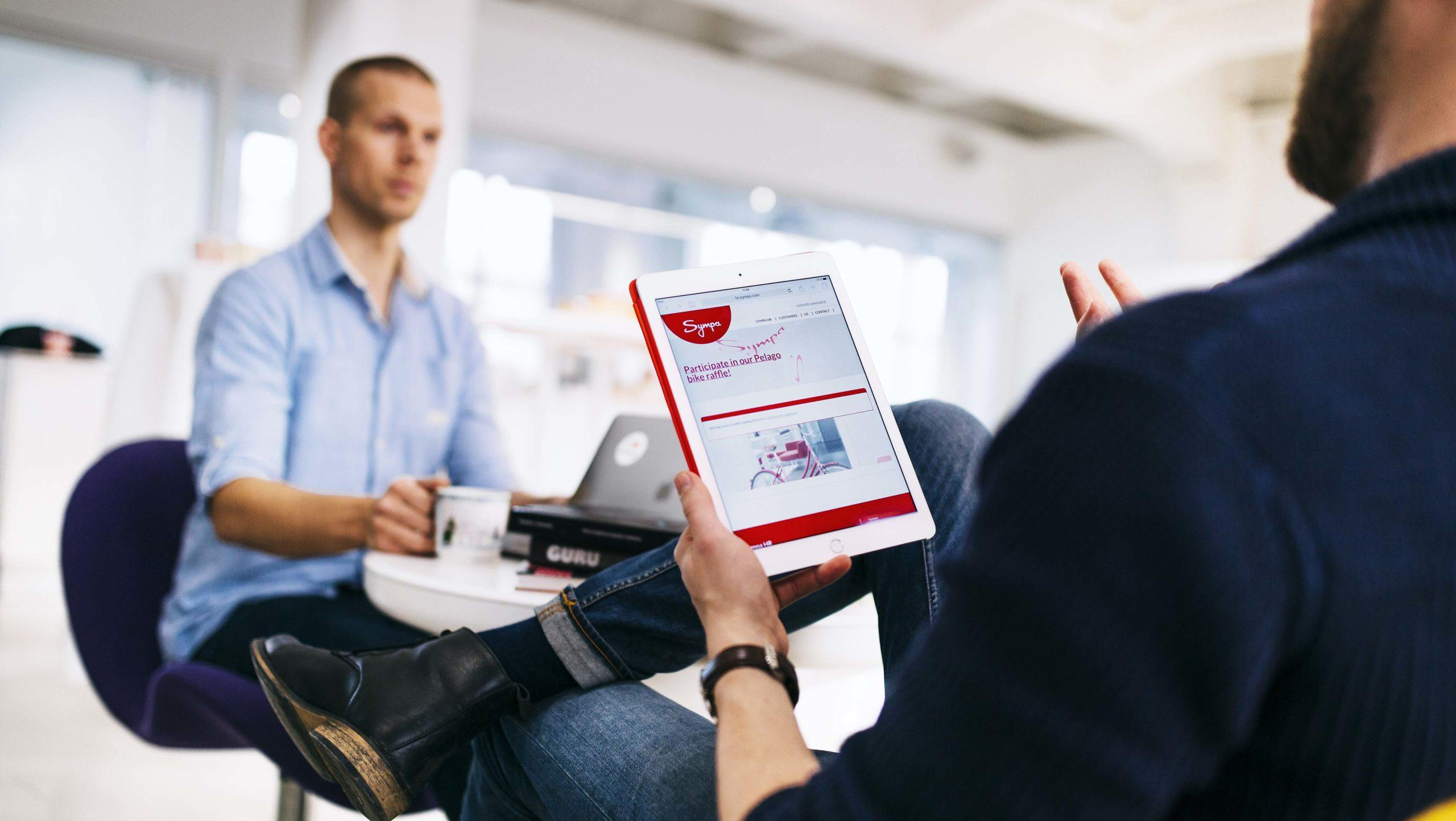 Man holding an ipad with Sympa HR page talks to a colleague