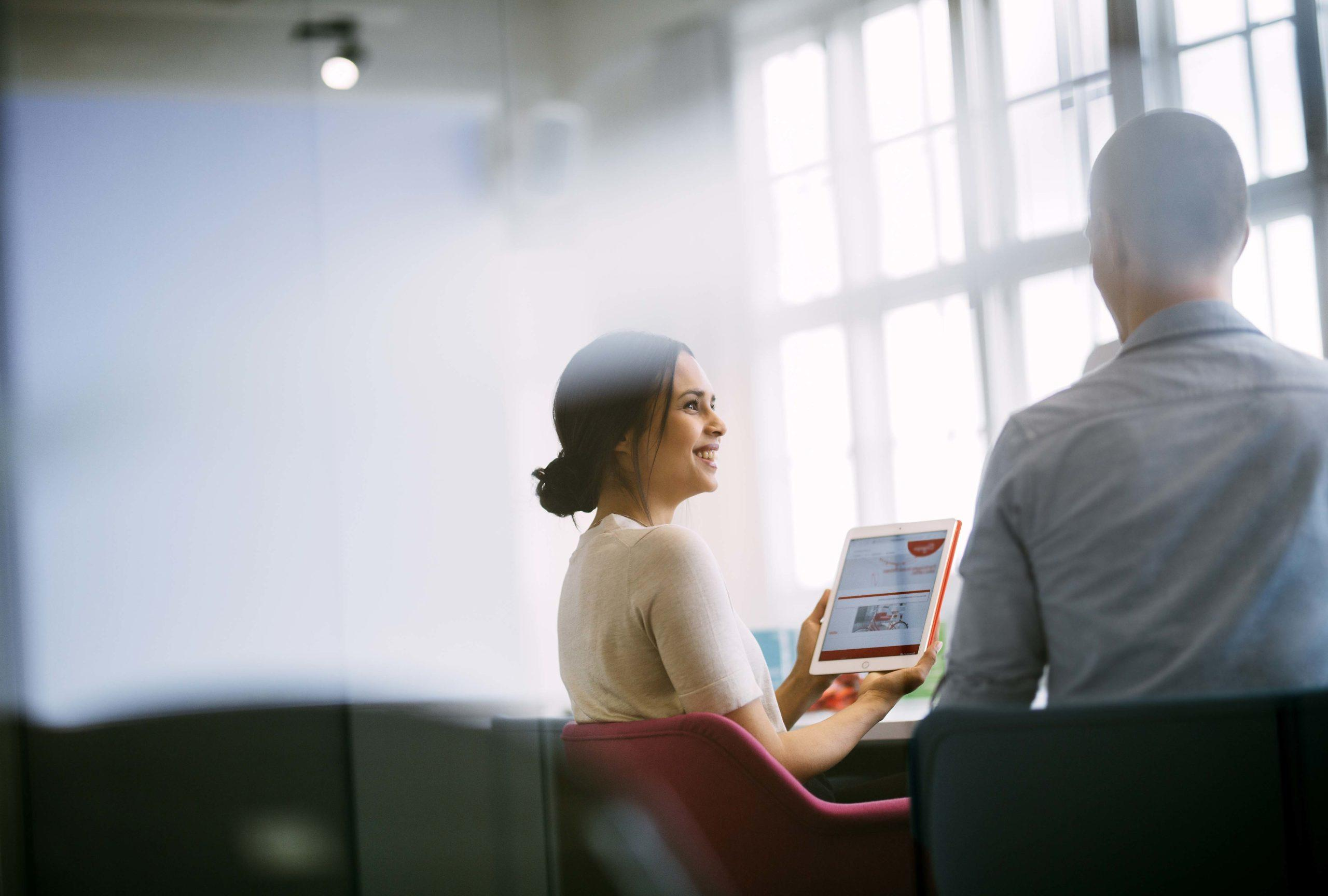 Woman showing ipad screen to a man at the office