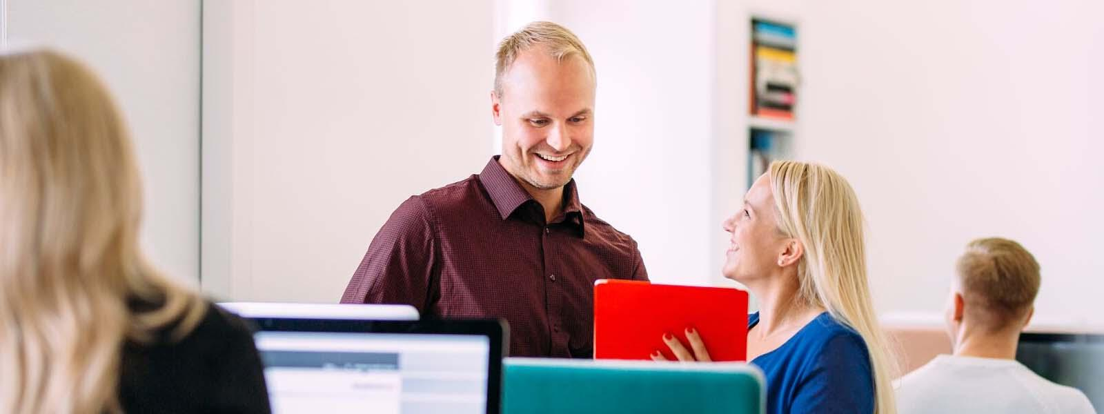 Woman with red notebook talks to a man and both smiling