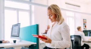 Female in white shirt holding a red ipad in the office