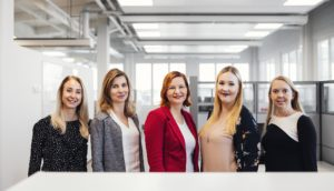 Five women standing at the office smiling